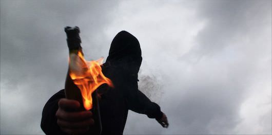 A reenactment from 'Informant' of a man throwing a molotov cocktail. Courtesy Jamie Meltzer