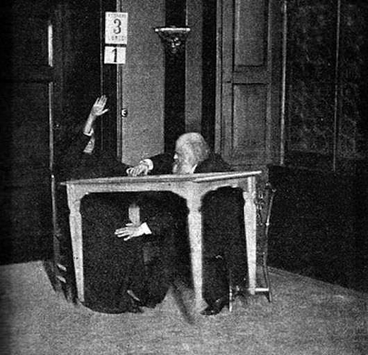 "Aksakov (right) monitors for fraud while medium Eusapia Palladino ""levitates"" a table, Milan, 1892."