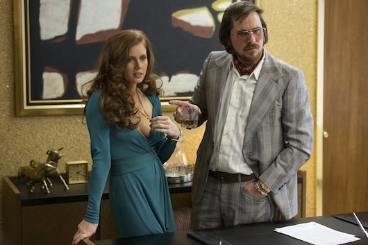 Sydney Prosser (Amy Adams, left) and Irving Rosenfeld (Christian Bale) attempt to scam an under cover agent, and they look good doing it. Courtesy Columbia Pictures