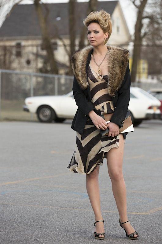 Rosalyn Rosenfeld (Jennifer Lawrence) outside the Long Island elementary school.  Her dress, jacket, jewelry, shoes, & bag are vintage.