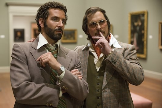 Richie Dimaso (Bradley Cooper, left) and Irving Rosenfeld (Christian Bale) talk in a gallery at the Frick Museum. Courtesy Columbia Pictures.