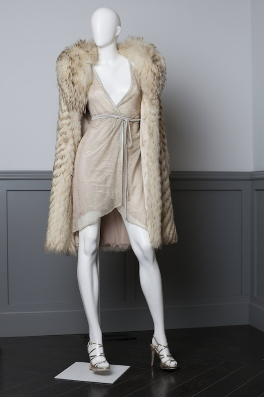 Costume design by Michael Wilkinson. Sheer platinum lame disco dress, worn by Amy Adams in scene at Studio 54. Made for the film. Vintage knee length fur with shawl collar.  Badgley Mischka disco-inpsired strappy stilettos
