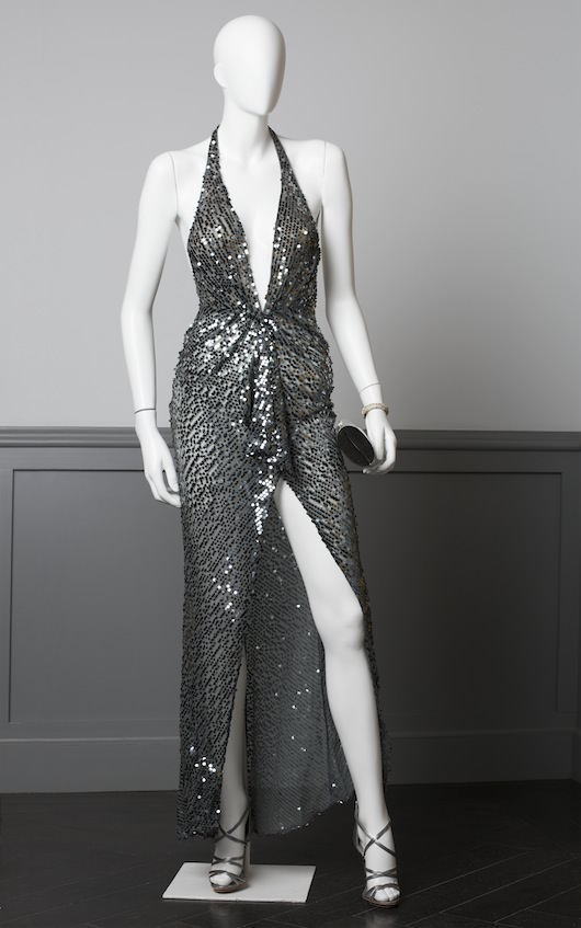 Sheer gunmetal sequin evening gown, worn by Amy Adams. Halterneck, backless, with high center front slit. Made for the film.   Badgley Mischka disco-inspired strappy stilettos,  Vintage Designer reptile silver clutch by Coblentz Originals (provided by Dressing Vintage). Costume design by Michael Wilkinson. Courtesy Columbia Pictures.
