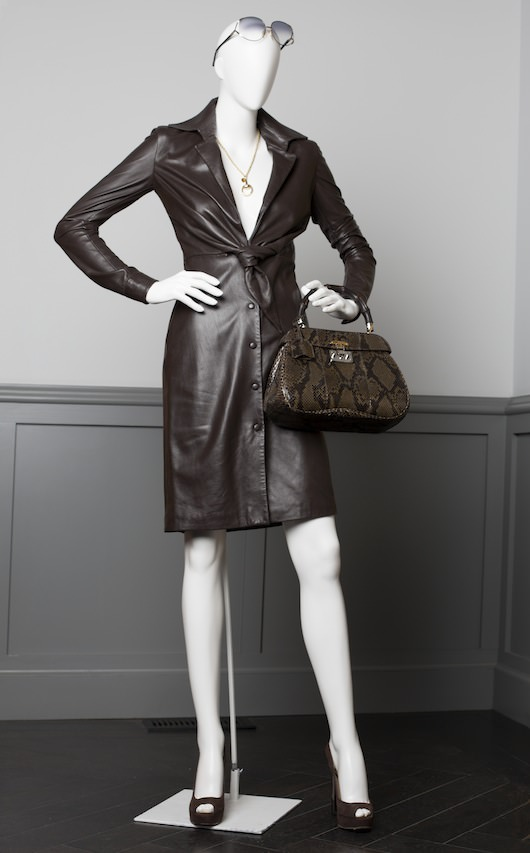 Costume design by Michael Wilkinson. Chocolate Leather deep plunge dress (Halston archvies), Gold Classic Horsebit Necklace (Gucci), Brown suede platform slingback heels,  Vintage Christian Dior sunglasses (provided by Allyn Scura Eyeworks),  Python & Bamboo Gucci Ladylock Handbag (Gucci Ladylock Bag).