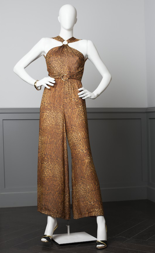 Vintage I. Magnin Leopard print chiffon halter neck jumpsuit, with gold ring detail at neck. Worn by Jennifer Lawrence at scene in Italian Restaurant. Vintage Xavier Danuad Paris stilettos. Costume design by Michael Wilkinson. Courtesy Columbia Pictures.