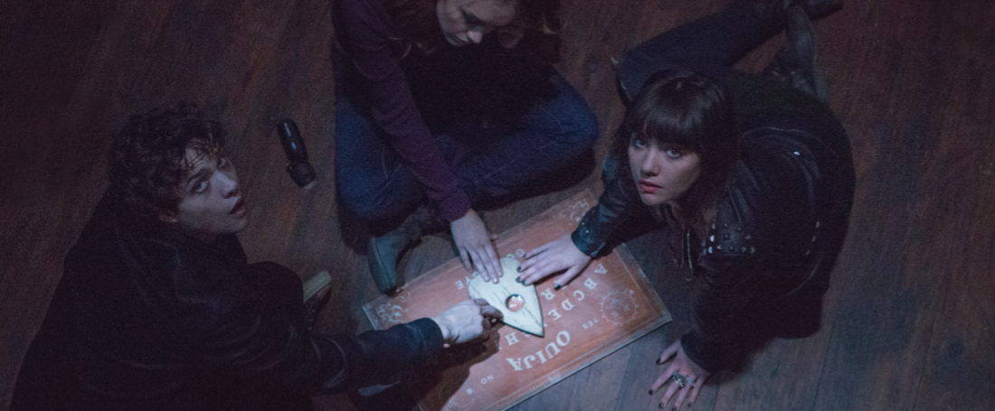 "(L to R) Pete (DOUGLAS SMITH), Laine (OLIVIA COOKE) and Sarah (ANA COTO) play the game in ""Ouija"", a supernatural thriller about a group of friends who must confront their most terrifying fears when they awaken the dark powers of an ancient spirit board."