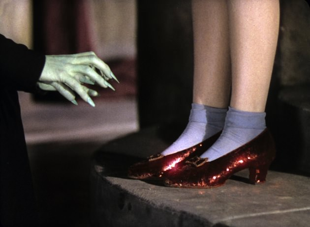 """Dorothy (Judy Garland) wore the most famous shoes in the world. Costume designer Adrian. """"It's unknown how many pairs of the shoes were made, but it's believed four pairs used in the film still exist today. The surviving pairs were made in sizes 5C, 5.5 and 6B to accommodate Judy Garland, her stand in and stunt double. The slippers began as white silk pumps made by the Innes Shoe Company in Los Angeles, and they were later dyed red at MGM Studios before being covered with fabric that had been hand-sewn with approximately 2,300 sequins. Each red leather bow, designed especially by Adrian, sparkles with red glass stones and bugle beads."""" Courtesy 'Hollywood Costume' exhibit."""