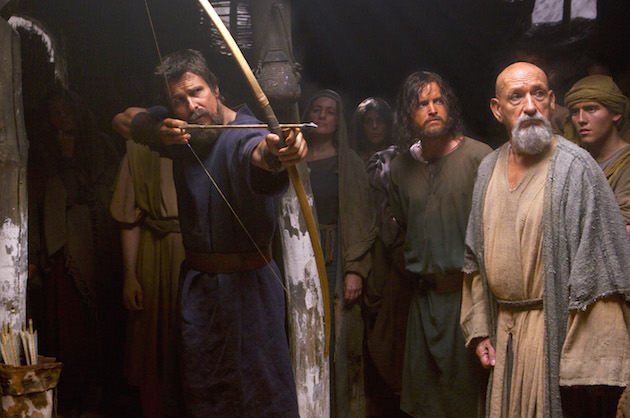 Moses (Christian Bale) displays his prowess with a bow and arrow, as Joshua (Aaron Paul, center) and Nun the scholar (Ben Kingsley) watch. Courtesy 20th Century Fox.