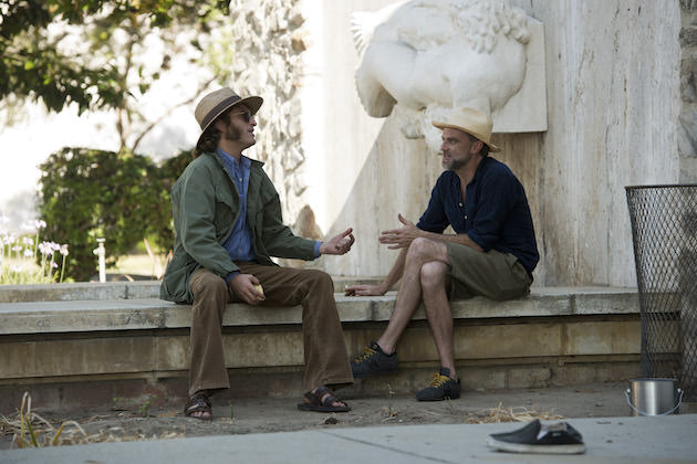 Joaquin Phoenix plays Pynchon's hero, Doc Sportello, sitting on location with director Paul Thomas Anderson. Courtesy Warner Bros. Pictures.