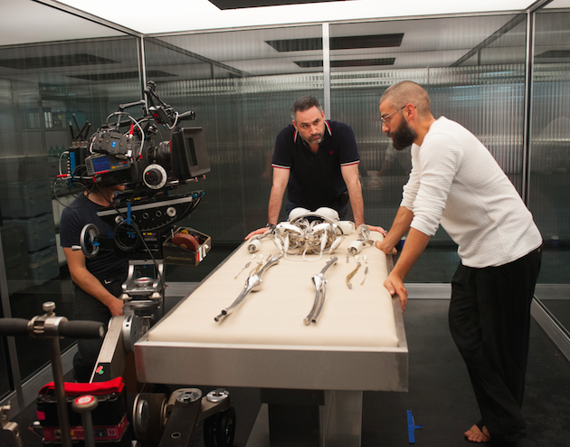 DP Rob Hardy, Garland and Isaac stand over Ava's robotic skeleton. Courtesy A24.
