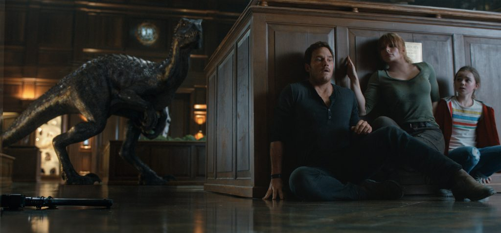 "The Indoraptor stalks its prey—(L to R) Owen (CHRIS PRATT), Claire (BRYCE DALLAS HOWARD) and Maisie (ISABELLA SERMON) in ""Jurassic World: Fallen Kingdom."" When the island's dormant volcano begins roaring to life, Owen and Claire (Bryce Dallas Howard) mount a campaign to rescue the remaining dinosaurs from this extinction-level event. Welcome to ""Jurassic World: Fallen Kingdom."" Photo Credit: Universal Studios and Amblin Entertainment, Inc. and Legendary Pictures Productions, LLC."