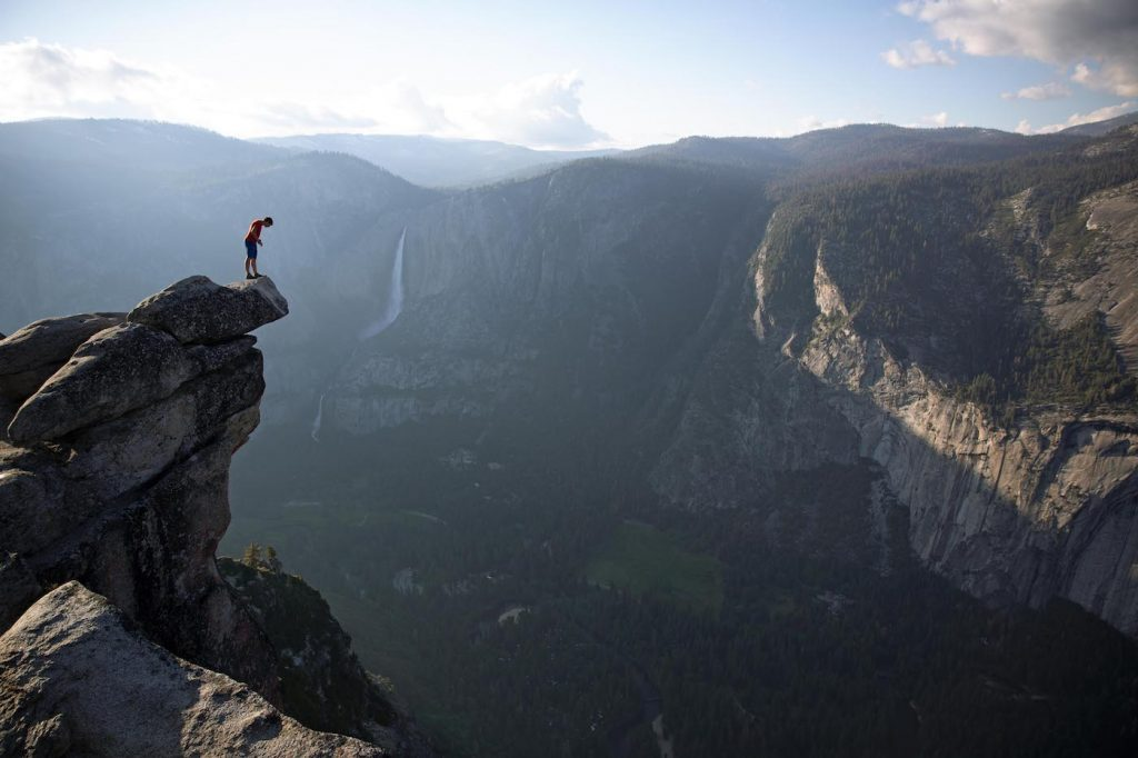 Alex Honnold peers over the edge of Glacier Point in Yosemite National Park. He had just climbed 2000 feet up from the valley floor. National Geographic/Jimmy Chin.