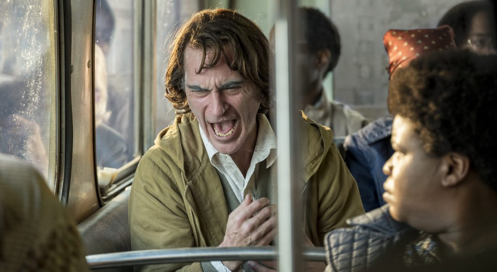 "Caption: (Center) JOAQUIN PHOENIX as Arthur Fleck in Warner Bros. Pictures, Village Roadshow Pictures and BRON Creative's tragedy ""JOKER,"" a Warner Bros. Pictures release. Photo Credit: Niko Tavernise. Copyright: © 2019 Warner Bros. Entertainment Inc."