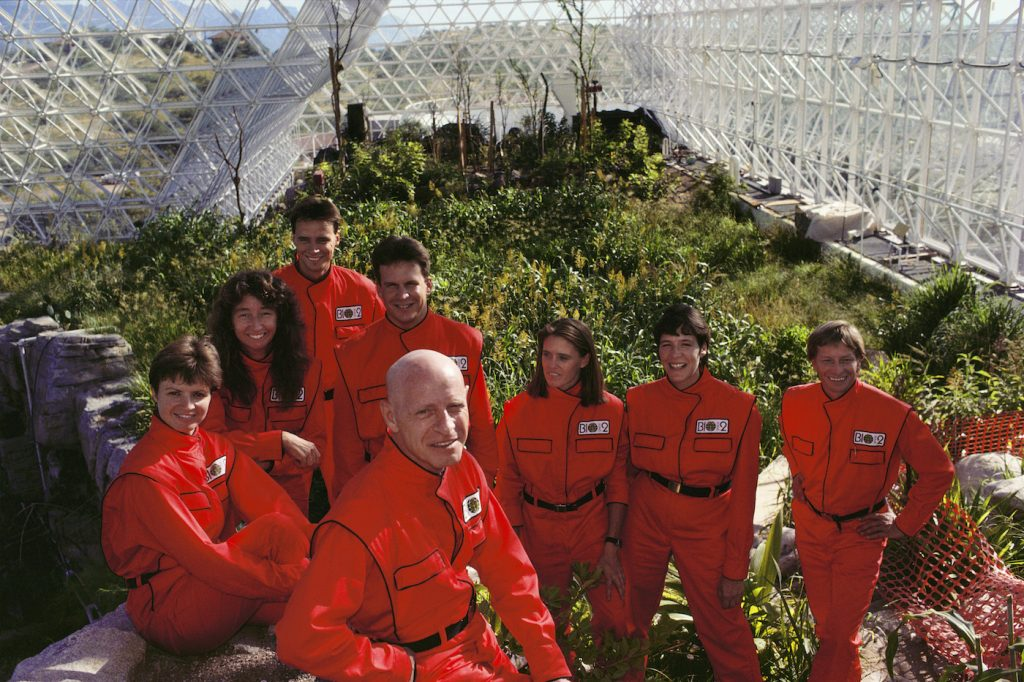Biosphere 2 Project undertaken by Space Biosphere Ventures, a private ecological research firm funded by Edward P. Bass of Texas. Candidates for (1990)'s Biosphere 2 project. Dr. Roy Walford (bald) is front and center. Biosphere 2 was a privately funded experiment, designed to investigate the way in which humans interact with a small self-sufficient ecological environment, and to look at possibilities for future planetary colonization. The $30 million Biosphere covers 2.5 acres near Tucson, Arizona, and was entirely self- contained. The eight 'Biospherian's' shared their air- and water-tight world with 3,800 species of plant and animal life during their two-year isolation experiment. The project had problems with oxygen levels and food supply, and has been criticized over its scientific validity.(1989)