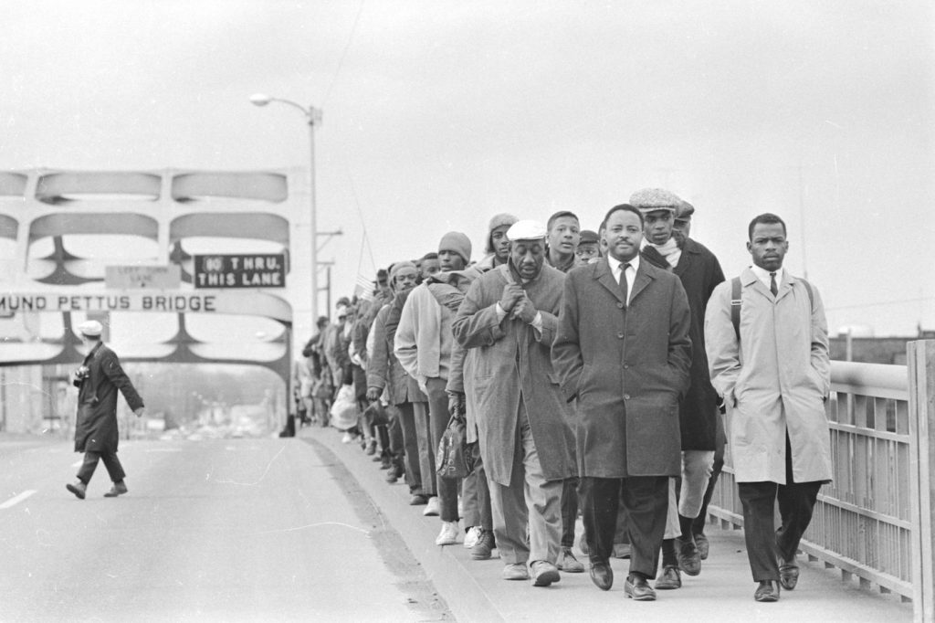 John Lewis with fellow protestors at Edmund Pettus Bridge, in JOHN LEWIS: GOOD TROUBLE, a Magnolia Pictures release. © Alabama Department of Archies and History. Donated by Alabama Media Group. Photo by Tom Lankford, Birmingham News. Photo courtesy of Magnolia Pictures.