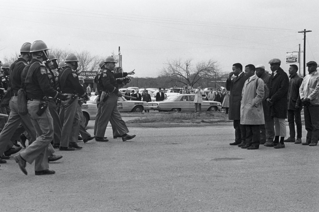 Protestors and police officers on Bloody Sunday, in JOHN LEWIS: GOOD TROUBLE, a Magnolia Pictures release. © Spider Martin. Photo courtesy of Magnolia Pictures.