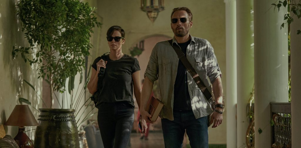THE OLD GUARD (L to R) CHARLIZE THERON as ANDY and MATTHIAS SCHOENAERTS as BOOKER in THE OLD GUARD. Cr. AIMEE SPINKS/NETFLIX © 2020