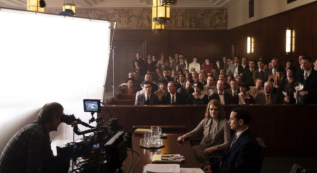 Camera operator Don Devine lines up a shot of Matthew Rhys (Perry Mason) and Gayle Rankin (Emily Dodson) in the Courtroom set on Paramount Stage 27, as background cast performs behind them.  The best background are ones audiences don't even notice, Mollie Stallman notes. Photo by Merrick Morton/HBO.