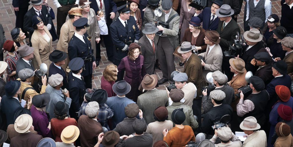 Matthew Rhys (Perry Mason) and Della Street (Juliet Rylance) are surrounded by a variety of background cast, portraying press, police and other onlookers, after the verdict is read in the show's season finale