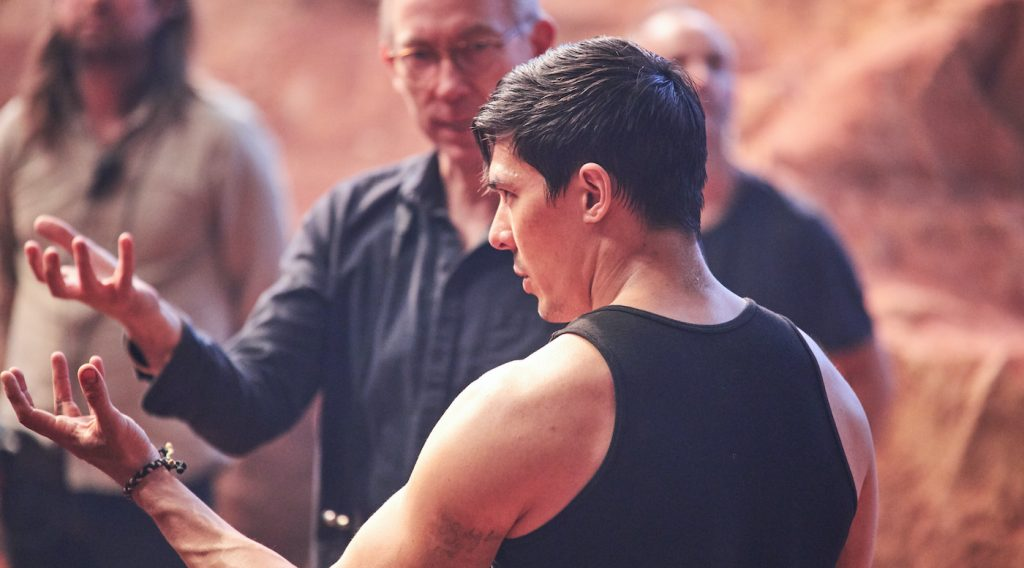 """Caption: (L-r Center Frame) Director SIMON MCQUOID and LEWIS TAN on the set of New Line Cinema's action adventure """"Mortal Kombat,"""" a Warner Bros. Pictures release. Photo Credit: Simon Westlake"""