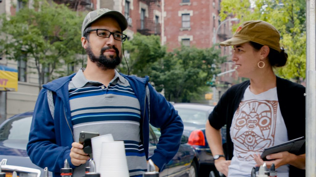 """Caption: (L-r) Concept/music & lyrics/producer LIN-MANUEL MIRANDA and QUIARA ALEGRÍA HUDES on the set of Warner Bros. Pictures' """"IN THE HEIGHTS,"""" a Warner Bros. Pictures release. Photo Credit: Courtesy of Warner Bros. Pictures"""