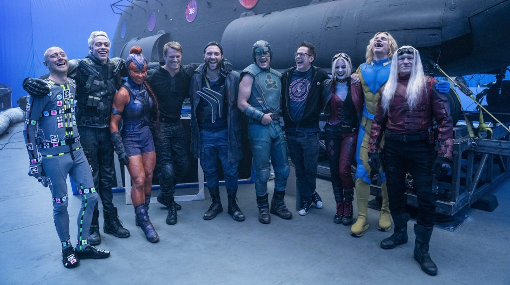 """Caption: (L-r) SEAN GUNN, PETE DAVIDSON, MAYLING NG, JOEL KINNAMAN, JAI COURTNEY, NATHAN FILLION, writer/director JAMES GUNN, MARGOT ROBBIE, FLULA BORG and MICHAEL ROOKER on the set of Warner Bros. Pictures' action adventure """"THE SUICIDE SQUAD,"""" a Warner Bros. Pictures release. Photo Credit: Jessica Miglio/™ & © DC Comics"""