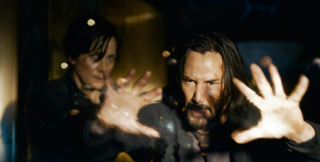 """Caption: (L-r) CARRIE-ANNE MOSS as Trinity and KEANU REEVES as Neo/Thomas Anderson in Warner Bros. Pictures, Village Roadshow Pictures and Venus Castina Productions' """"THE MATRIX RESURRECTIONS,"""" a Warner Bros. Pictures release. Photo Credit: Courtesy of Warner Bros. Pictures"""